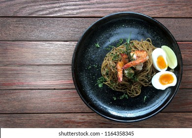 asian food design spaghetti shrimp with basil leaf and boil egg, lime  on brown hard wood table texture on background.