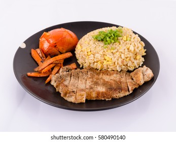 Asian food egg fried rice with roasted pork, grilled tomato and carrots. Full dish for lunch or dinner. Steak cooked Thai style.