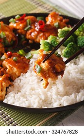 Asian food: General Tso's chicken with rice for dinner. vertical, macro