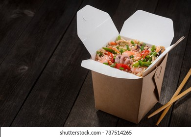 Asian food to go. Opened box of rice with seafood and vegetables, prepared in wok, and chopsticks on wooden table. Space in the left to insert your text.