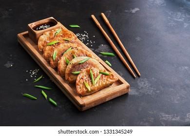 Asian food homemade fried dumplings on a dark background. Korean dumplings. Selective focus