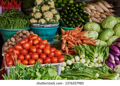 Asian food ingredients corner. Organic fresh agricultural product at farmer market. Fresh tomatoes, onions, eggplant, are packaged in simple containers and displayed for sale at an produce stand.