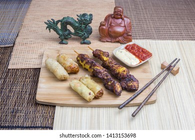 Asian food: nems with chicken skewers, served with asian decoration.