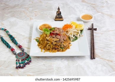 Asian food, Pad Thai beef dishes with sauces, on a white square plate. Served on a marble table.