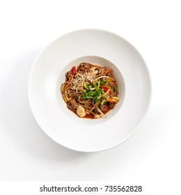 Asian food restaurant. Buckwheat noodles with chicken vegetables sprinkled with fresh herbs and sesame seeds in white plate. Top view