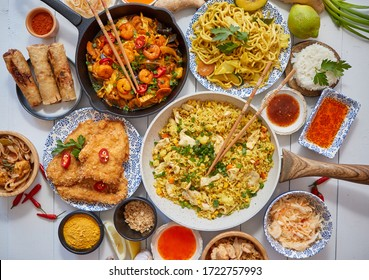 Asian food served. Plates, pans and bowls full of tasty oriental dishes. Noodles chicken stir fry and vegetables ingredients with spices, sauces and chopsticks on whie wooden background.