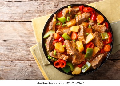 Asian food: Stewed beef with potatoes, peppers, peas, tomatoes and carrots close-up on a plate on the table. horizontal top view from above