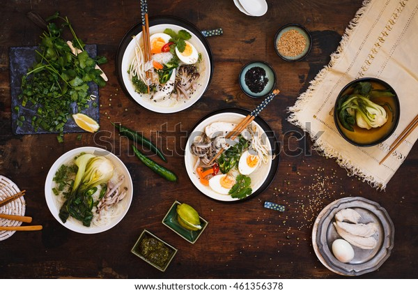 Asian food table. Overhead of asian food table with hot ramen soup bowl and variety fresh ingredients over wooden table.