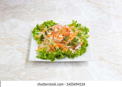Asian food, Thai papaya salad with shrimp, onion, salad and grated carrot, on a white square plate. Served on a marble table.