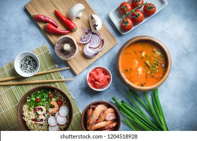 Asian food, Tom Yam and Ramen with shrimps, Thai food in wooden bowl, Egg noodles, Preparation, Chilli peppers, onion and mushrooms, Spicy, Top view on light gray background