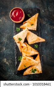 Asian food. Vegetarian samsa (samosas) with tomato sauce. Dark blue background copy space top view