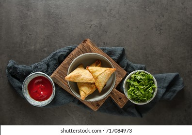 Asian food. Vegetarian samsa with tomato sauce and herbs. Dark background