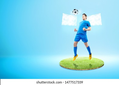 Asian football player man jump and heading the ball on the football field with spotlights