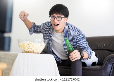 Asian football supporters group of friend watching soccer sport match on tv and cheering, celebrating with beer and popcorn at home with fun or disappoint emoticon.