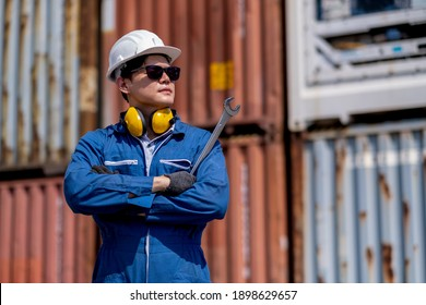 Asian Foreman or cargo container worker with holding wrench stand in front of container stack and confidence or arm-crossed action. Business Logistics import export shipping concept.