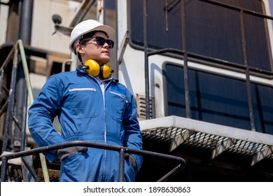 Asian Foreman or cargo container worker with confidence action stand on side of truck in workplace area. Business Logistics import export shipping concept.