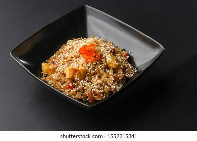 Asian fried rice with eggs, pineapple and sesame close-up on a plate, horizontal view from above. Nigerian food party: Jollof rice with fried chicken close-up on a plate.