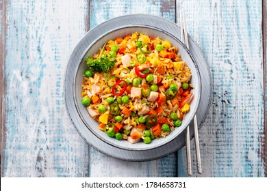 Asian fried rice with ham. Blue wooden background. Close up. Top view.