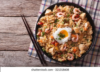 Asian fried rice nasi goreng with chicken, prawns, egg and vegetables horizontal view from above