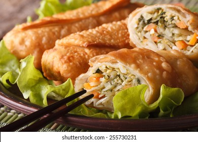 Asian fried spring rolls sliced on a plate macro and chopsticks. horizontal