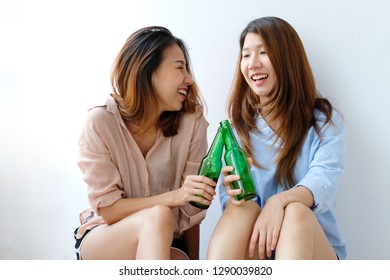 Asian friend drink beer, Two asian women holding alcohol bottle smiling with happiness, Asia friend drinking beer sitting together at party, LGBT couple, lifestyle