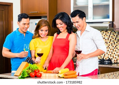 Asian friends cutting vegetables cooking together in domestic kitchen for dinner party, drinking wine