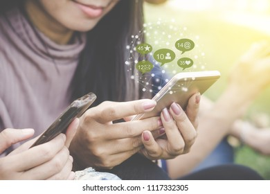 Asian friends hand holding smart phone having fun with technology social media and network icon background