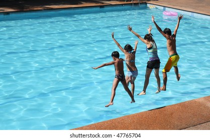 asian friends jumping on the swimming pool