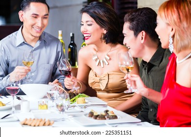 Asian friends, two couples, dining in fancy restaurant eating good food and drinking wine