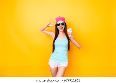 Asian funky hipster is posing for photo, wearing tourist`s outfit, glasses, hat, holds ice cream, so slim, attractive and  imposing!