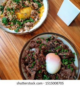 Asian fusion food on wooden table.Thinly sliced fatty beef cooked in soy sauce and served over rice with a raw egg yolk on top.Fried pork with chilli and holy basil on creamy omelet cover on rice.