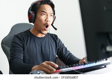 Asian Gamer playing mobile game with exited expression. Winning esport game