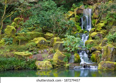 Asian Garden Waterfall flowing into a still pond surrounded by moss covered rocks, trees, and other foliage
