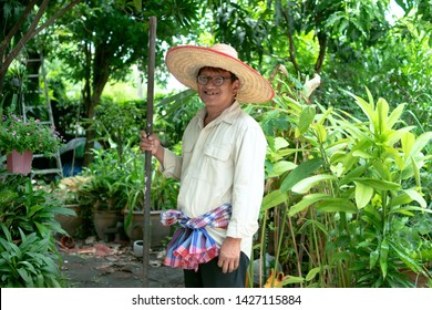 Asian gardener standing in garden. His wearing straw hat, white shirt, glasses and loincloth. His hand is holding equipment garden tool. It's shovel. Garden is green and shady. It is a day in summer.