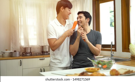 Asian gay couple homosexual cooking together in the kitchen