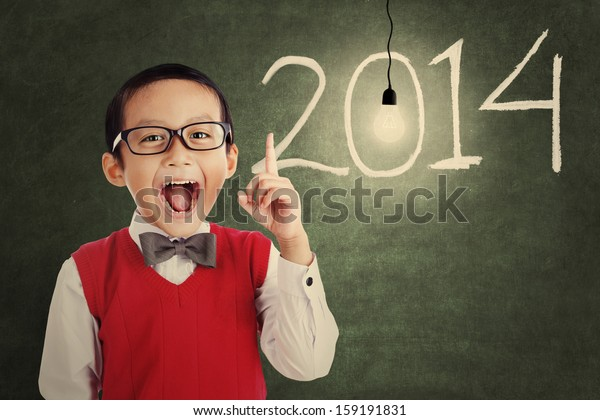 Asian genius student with light bulb and number of new year 2014 shot in a classroom