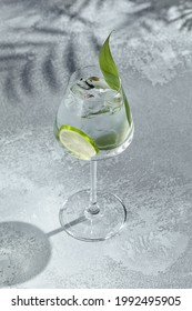 Asian Gin tonic cocktail for lifestyle design. Summer cocktail asian concept background. Gin tonic drink with lime slice and banana leaf. Cocktail in wine glass with palm leaf shadow - Shutterstock ID 1992495905