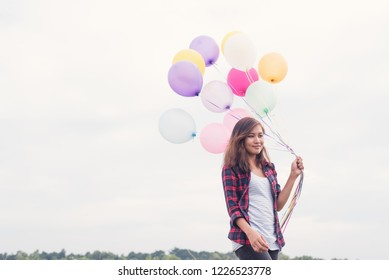 Asian girl with balloons in the field