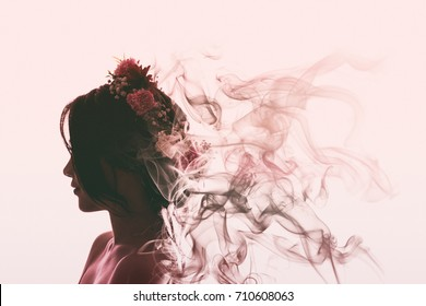 Asian girl is beautiful and charming with flowers crown. She is evaporating into perfume smoke. Pink tone.