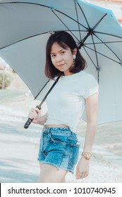 Asian girl with a beautiful white shirt standing poses with an umbrella and smiling.