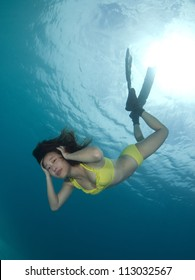 Asian girl in bikini swims underwater