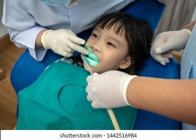 Asian girl biting silicon tray of Fluoride and dental saliva suction.