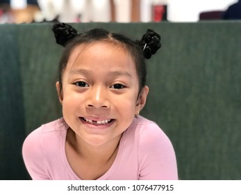 Asian girl black hair Chinese hair style smiling with lost teeth