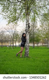 Asian girl in black jacket standing near birch tree at the park