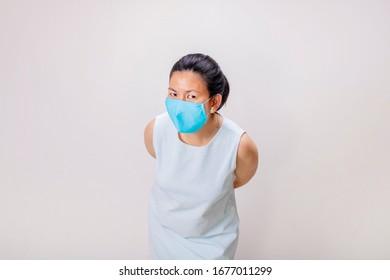 スタジオで青いタンクの上にアジア人の女の子が青いマスクを着る
