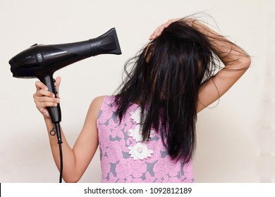 asian girl b;ow her hairs by herself