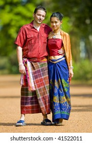 asian girl and caucasian man wearing traditional thai clothes