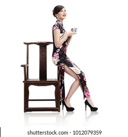 Asian girl in cheongsam holds a cup of tea in the chair