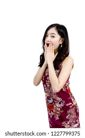 An Asian girl in Cheongsam or Qipao dress is smiling and happy emotion to you in Chinese New Year festival concept.
