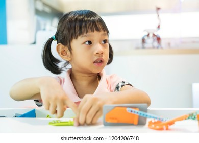 asian girl child having fun playing with colorful plastic blocks indoor at play school